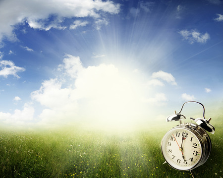 Alarm clock in sunlit spring field photo