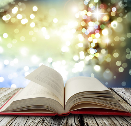 Open book on table in front of bright lights Stockfoto