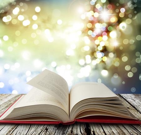 Open boek op tafel voor felle lichten Stockfoto