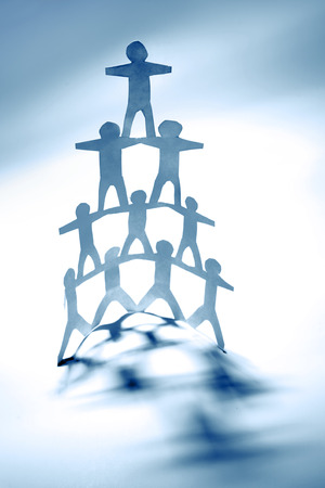 Team of paper doll people, human pyramid photo