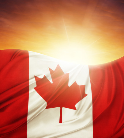 Canadian flag in front of bright sky