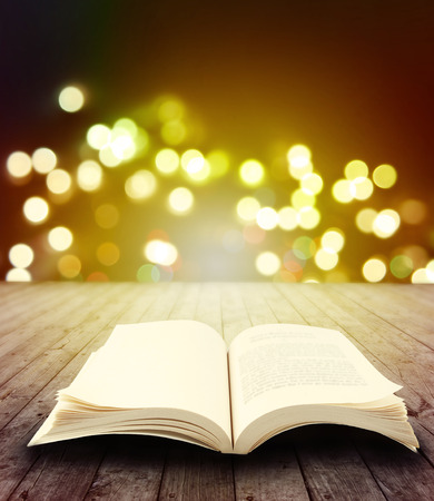 Open book on table in front of bright lights photo