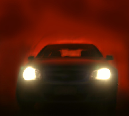 headlights: Bright headlights on car. Red background  Stock Photo