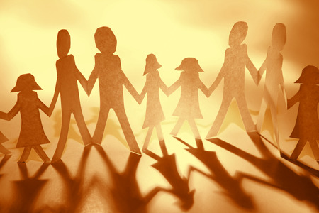 Team of paper doll people holding hands photo