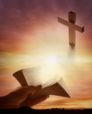Hand holding open book, cross in sky photo