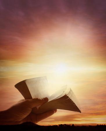 bible ouverte: Une main tenant livre ouvert dans le ciel