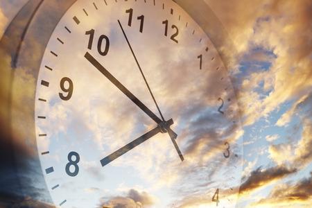 明るい空に時計の文字盤 写真素材
