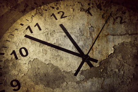 Closeup of hands on grunge clock face Stock Photo