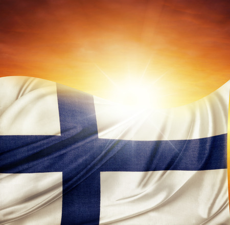 finnish: Finnish flag in front of bright sky Stock Photo