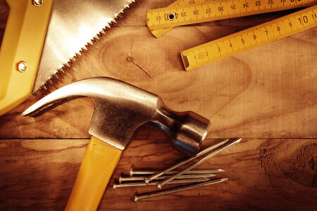 Hammer, nails, ruler and saw on wood photo