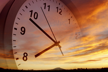 the passing of time: Clock face in bright sky Stock Photo