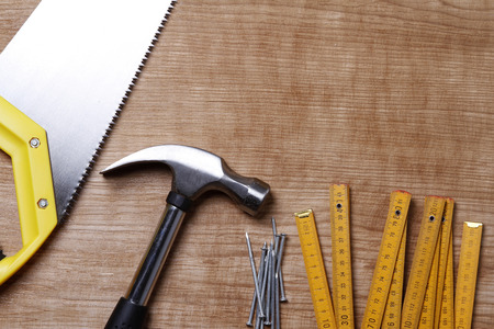 home improvement: Hammer, nails, ruler and saw on wood