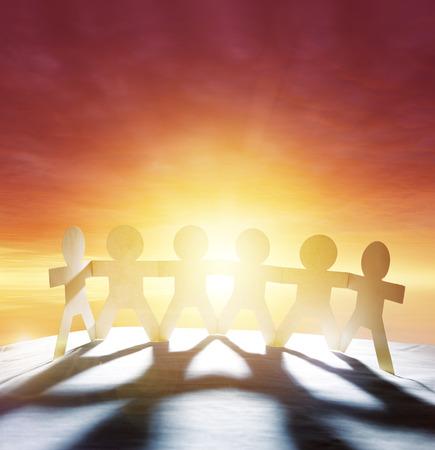 cogidos de la mano: Equipo de seis personas paperchain tomados de la mano en frente de cielo brillante Foto de archivo