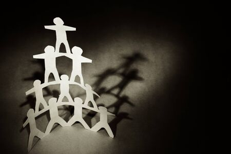 piramide humana: Pirámide de equipo humano sobre fondo oscuro