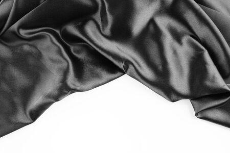 Closeup of rippled black silk fabric on plain background photo