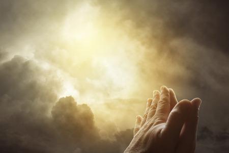 orando: Las manos juntas orando en el cielo brillante