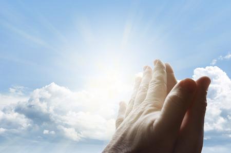 Hands together praying in bright sky Standard-Bild