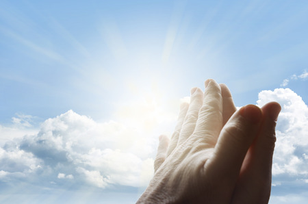 Hands together praying in bright sky Archivio Fotografico