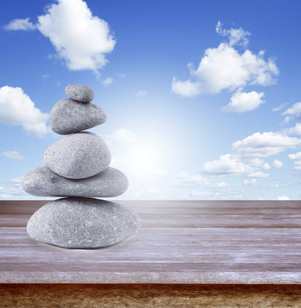 steadiness: Rocks balancing on table in front of blue sky