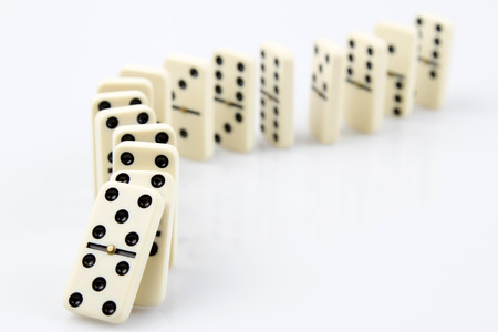 Dominoes on plain background, about to fall Archivio Fotografico