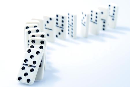 Dominostenen op effen achtergrond, op het punt om te vallen Stockfoto