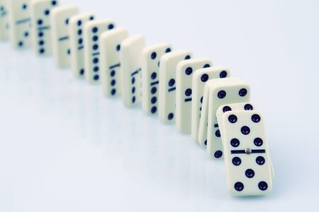 dominoes: Dominoes on plain background, about to fall Stock Photo