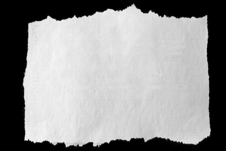 Piece of torn paper on black Standard-Bild
