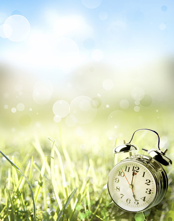 spring time: Alarm clock in spring field