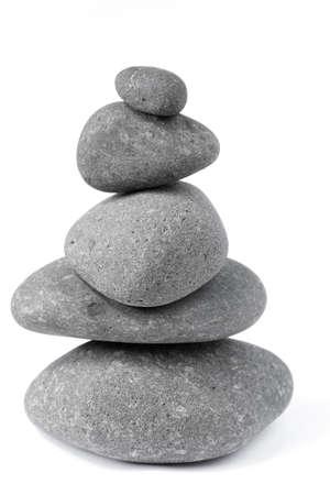steadiness: Pile of five balanced rocks on plain background