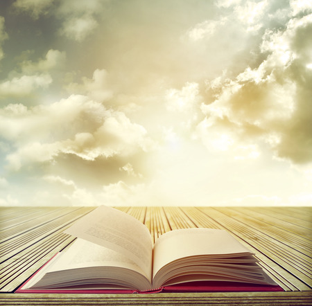cielos abiertos: Libro abierto en la mesa delante de cielo brillante