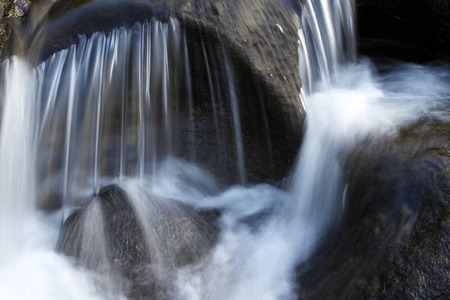 rushing water: Water flowing over rocks in stream Stock Photo