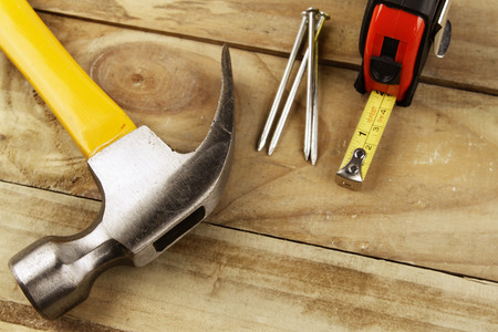 hammer and nails: Hammer, nails and tape measure on wood