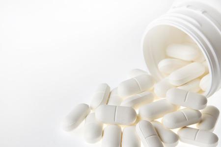 sobredosis: Píldoras derrame de un recipiente de plástico Foto de archivo