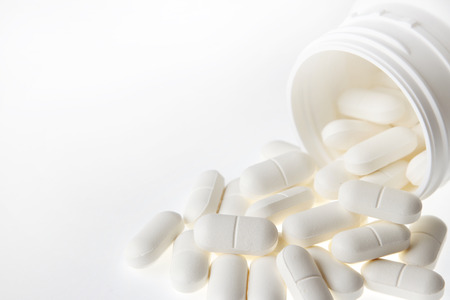 plastic container: Pills spilling from plastic container