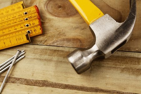 hammer and nails: Hammer, nails and folding ruler on wood