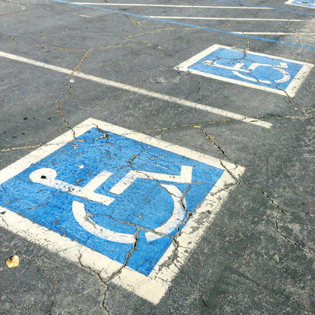 wheelchair access: Handicapped symbols painted on parking spaces
