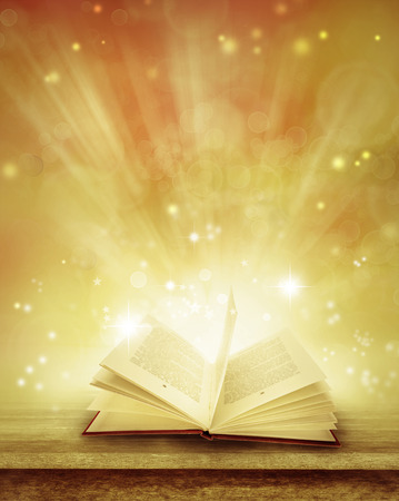 fairy story: Open book on table in front of magical background Stock Photo
