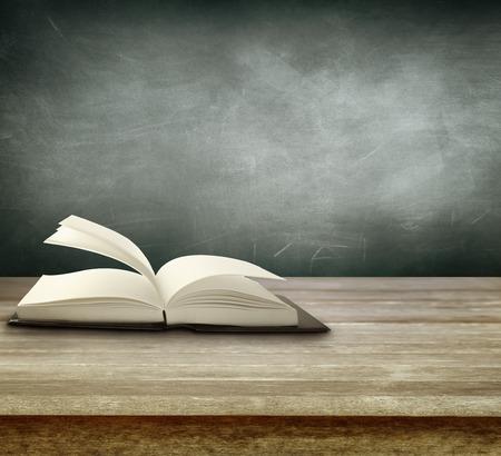 Ouvrir le livre sur la table en face de tableau noir Banque d'images - 43596413