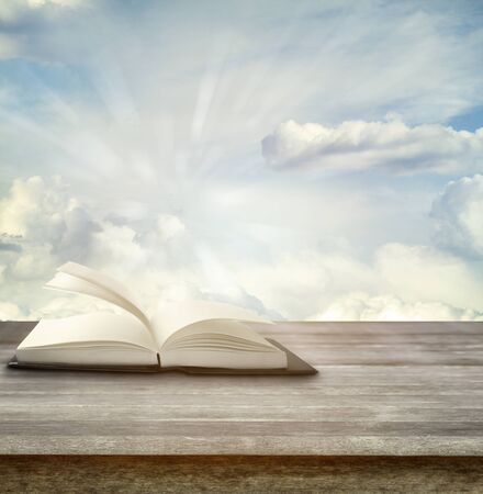 book concept: Open book on deck in front of sky