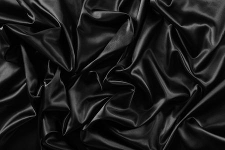 テクスチャー: 波状の黒い絹の布のクローズ アップ