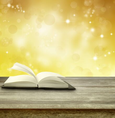 one story: Open book on table in front of magical background Stock Photo