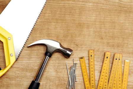 hammer and nails: Hammer, nails, ruler and saw on wood. Copy space