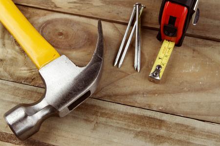 herramientas de construccion: Martillo, clavos y cinta métrica en la madera