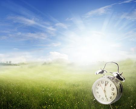 ahorros: reloj de alarma en la primavera de campo iluminado por el sol Foto de archivo