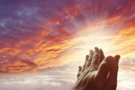 Hands together praying in bright sky Foto de archivo