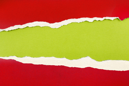 緑の背景に赤の紙に穴をリッピングしました。コピー スペース 写真素材