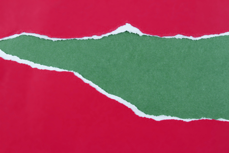 paper rip: Hole ripped in red paper on green background. Copy space