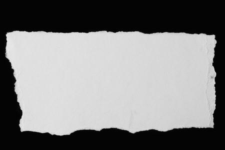 Piece of torn paper on black Foto de archivo