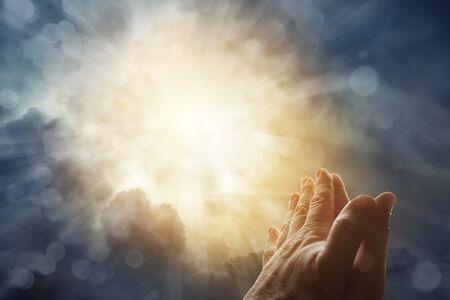 Las manos juntas orando en el cielo brillante