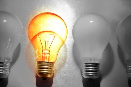 bombilla: Una bombilla brillante en la línea de bombillas sin brillo. Destacándose concepto